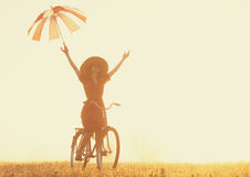 Girl with umbrella on a bike Stock Image
