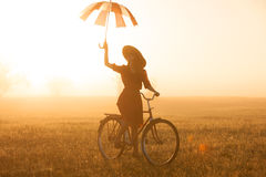Girl with umbrella on a bike Stock Photography