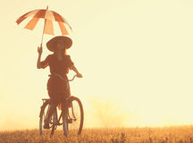 Girl with umbrella on a bike Stock Images