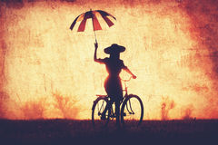 Girl with umbrella on a bike. In the countryside in sunrise time Royalty Free Stock Photos