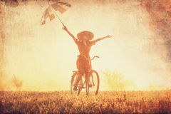 Girl with umbrella on a bike. In the countryside in sunrise time Stock Images