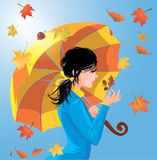 Girl with umbrella on blue sky background with leaves, autumn se Stock Image