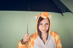 Girl with umbrella in a bright children`s pajamas in the form of a kangaroo. emotional portrait of a student. costume presentation stock photos