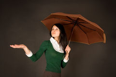 Girl with umbrella checking for rain. Girl in teacher or student outfit under umbrella Stock Image