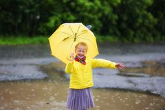 Little little girl in a yellow jacket and yellow boots with yellow umbrella in the rain. royalty free stock images