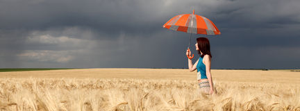 Girl with umbrella at field. Panoramic photo Royalty Free Stock Image