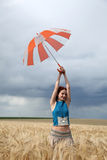 Girl with umbrella at field Stock Photos