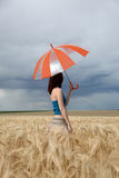 Girl with umbrella at field Stock Images