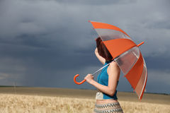 Girl with umbrella at field Stock Photo