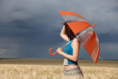 Girl with umbrella at field. Stock Photography