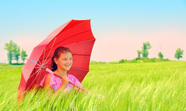 Girl with umbrella at field Stock Image