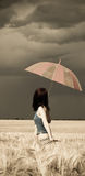 Girl with umbrella at field in retro style Stock Image