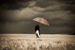 Girl with umbrella at field in retro style Royalty Free Stock Photography