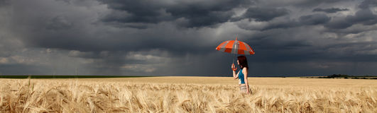 Girl with umbrella at field. in storm. Girl with umbrella at field. Panoramic photo Stock Photos