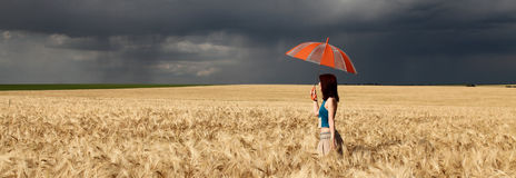 Girl with umbrella at field. in storm. Girl with umbrella at field. Panoramic photo Royalty Free Stock Image