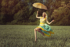 Girl with an umbrella levitates. Girl levitates over the green field on the umbrella. She is wearing a nice summer dress Royalty Free Stock Photos
