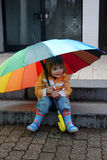 Girl with umbrella. Little girl  outside with a colorful big umbrella Stock Photography