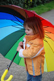 Girl with umbrella. Little girl  outside with a colorful big umbrella Stock Photos
