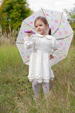 Girl with Umbrella. Little girl in a white dress stands with an umbrella in the autumn meadow stock photos