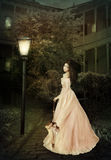 Girl with umbrella. A girl in a long dress with an umbrella under the light of a street lamp on the background of an old house Royalty Free Stock Image