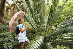 Girl With Umbrella Looking At Large Fern Stock Photo