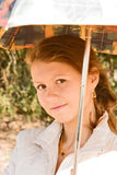 A girl with an umbrella. A pretty girl dressed in a white jacket with a parasol Stock Photography