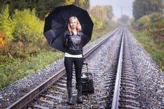 Girl, umbrella and rails Stock Image
