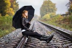 Girl, umbrella and rails Stock Photography
