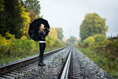 Girl, umbrella and rails Stock Images