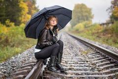 Girl, umbrella and rails Stock Photos