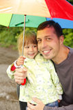 Girl with an umbrella in the rain with his father Royalty Free Stock Images