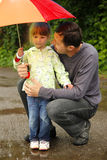 Girl with an umbrella in the rain with his father Royalty Free Stock Photography