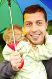 Girl with an umbrella in the rain with his father Stock Photography
