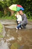Girl with an umbrella in the rain with his father Stock Photos