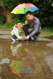 Girl with an umbrella in the rain with his father Stock Images