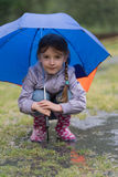 Girl with an umbrella in the rain playing Stock Photography