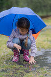 Girl with an umbrella in the rain playing Stock Image