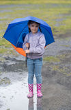 Girl with an umbrella in the rain playing Royalty Free Stock Photos