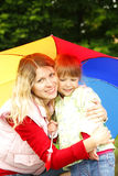 Girl with an umbrella in the rain playing with mom Stock Photo