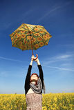 Girl with umbrella at rape field. Royalty Free Stock Photo