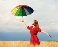Girl with umbrella. Redhead girl with umbrella at field Royalty Free Stock Photography