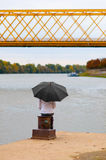 Girl with umbrella sitting on the dock's column Stock Images