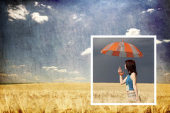 Girl with umbrella in storm at wheat field Stock Photo