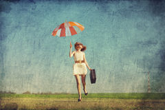 Girl with umbrella and suitcase Royalty Free Stock Images
