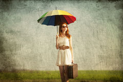 Girl with umbrella and suitcase Stock Photography