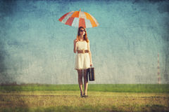 Girl with umbrella and suitcase Stock Image