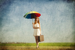 Girl with umbrella and suitcase Stock Images