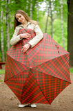 Girl with an umbrella in a summer park Stock Images