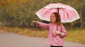 Girl With Umbrella Under Rain. Little girl is standing underneath an umbrella at rain stock footage