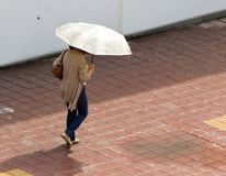 Girl with umbrella walking along paving stones Stock Images